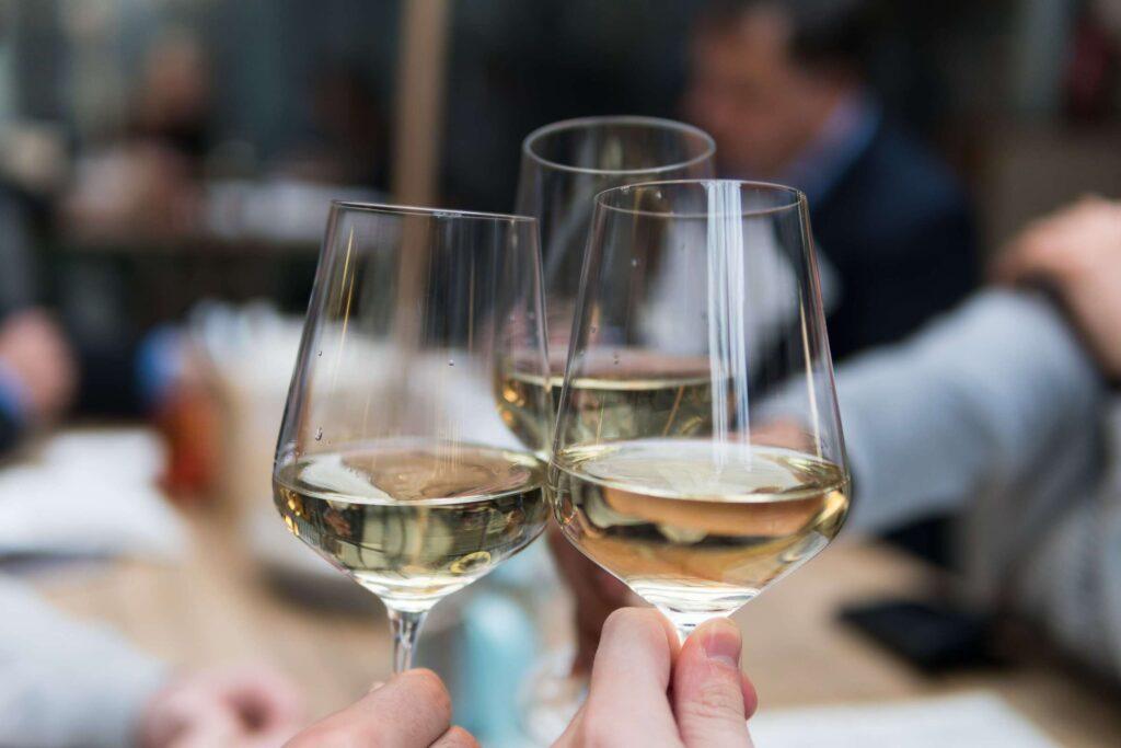 Amici brindano con tre calici di vino bianco Traminer aromatico Selva Bianca di Cantina Barchessa Loredan.