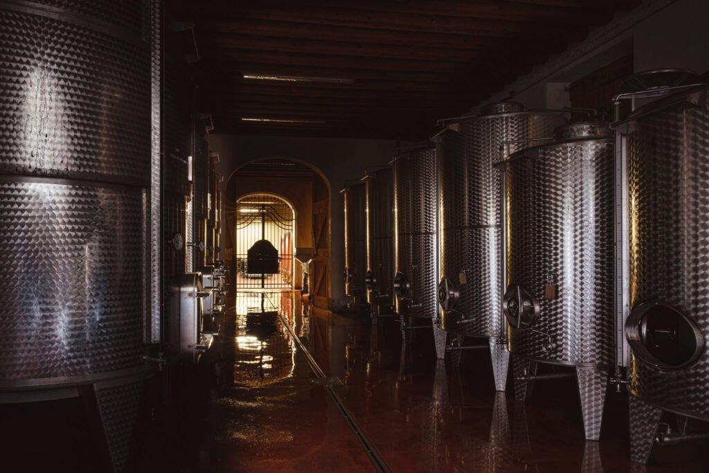 Le moderne botti di alluminio usate per la vinificazione dell'uva glera si riflettono sul pavimento della Cantina Barchessa Loredan.