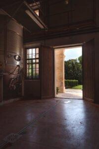 Vista dall'interno della cantina verso il giardino, tramite il portone del porticato.