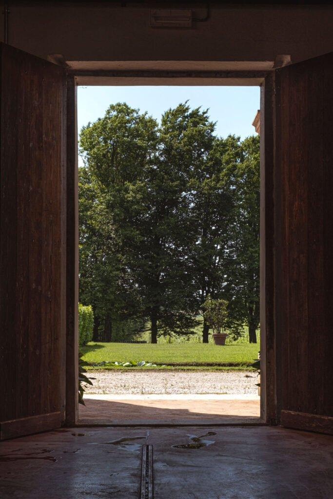 Vista sul giardino attraverso il maestoso portone di accesso ai locali della Cantina Barchessa Loredan.